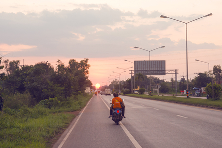 Car and motorcycle on road with clouds and a beautiful sunset
