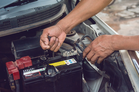 Car mechanic working Install battery with wrench in garage. Repair service. Stock fotó