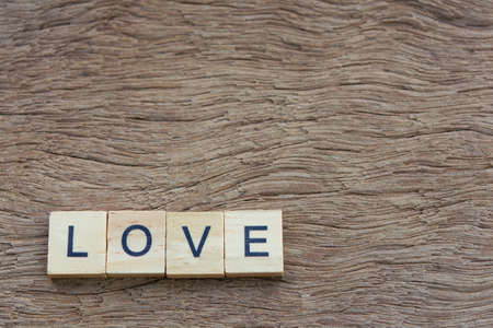 Text wooden blocks spelling the word love on wooden background