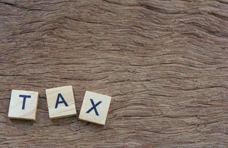 Tax with wooden alphabet blocks, on plank wooden background with copy space 免版税图像