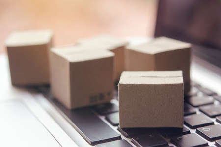 Online shopping - Paper cartons or parcel with a shopping cart on a laptop keyboard. Shopping service on The online web and offers home delivery.