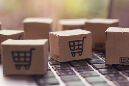 Online shopping - Paper cartons or parcel with a shopping cart on a laptop keyboard. Shopping service on The online web and offers home delivery. Archivio Fotografico
