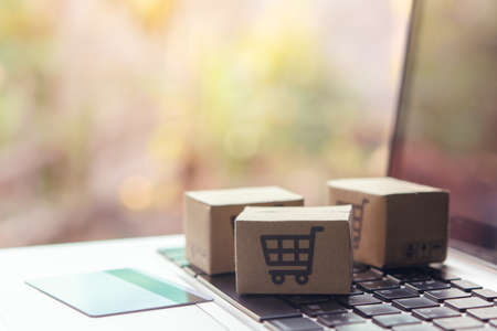 Online shopping - Paper cartons or parcel with a shopping cart and credit card on a laptop keyboard. Shopping service on The online web and offers home delivery.