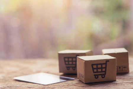 Online shopping - Paper cartons or parcel with a shopping cart and credit card on wood table top. Shopping service on The online web and offers home delivery.