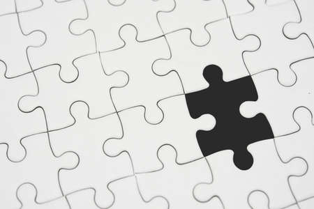 White jigsaw puzzle pattern background. placing last piece of jigsaw puzzle Stock Photo