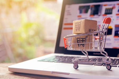 Shopping online concept - Parcel or Paper cartons with a shopping cart in a trolley on a laptop keyboard. Shopping service on The online web. offers home delivery. Banque d'images