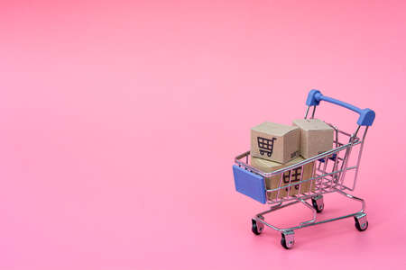 Shopping concept : Cartons or Paper boxes in blue shopping cart on pink background. online shopping consumers can shop from home and delivery service. with copy space