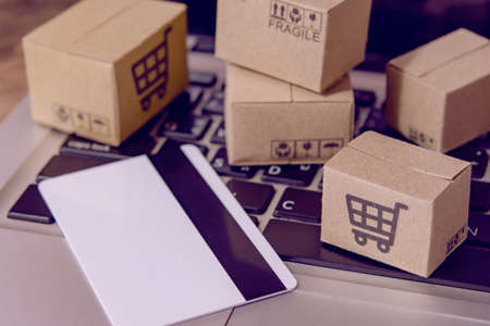 Shopping online. Credit card and cardboard box with a shopping cart logo on laptop keyboard. Shopping service on The online web. offers home delivery Banque d'images