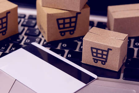 Shopping online. Credit card and cardboard box with a shopping cart icon on laptop keyboard. Shopping service on The online web. offers home delivery