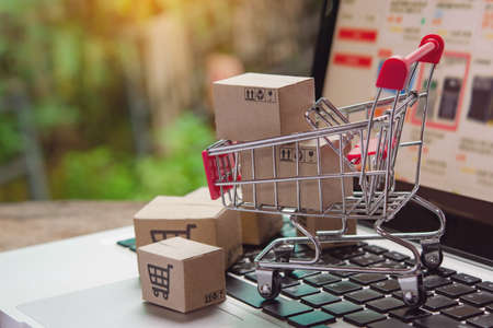 Shopping online. cardboard box with a shopping cart icon in a trolley on laptop keyboard. Shopping service on The online web. offers home delivery