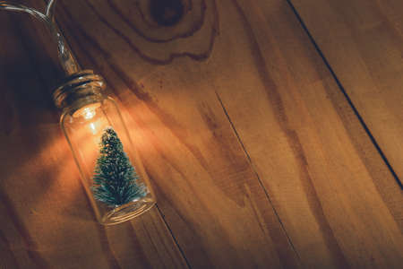 Light bulb and small Christmas tree in glass jar over wooden background