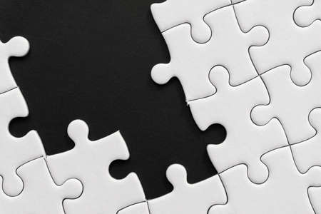 Unfinished white jigsaw puzzle pieces on black background