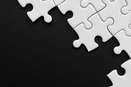 Unfinished white jigsaw puzzle pieces on black background with copy space