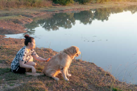 Woman and Golden retriever dog sitting near river or lake