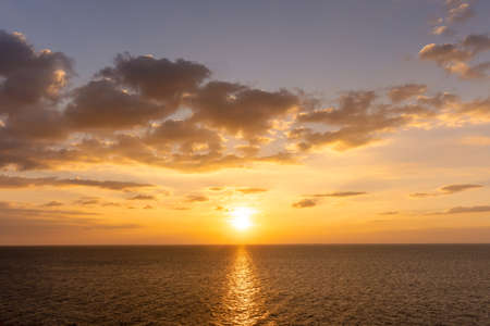 Sunset reflection ocean. beautiful sunset behind the clouds and blue sky above the over ocean landscape background