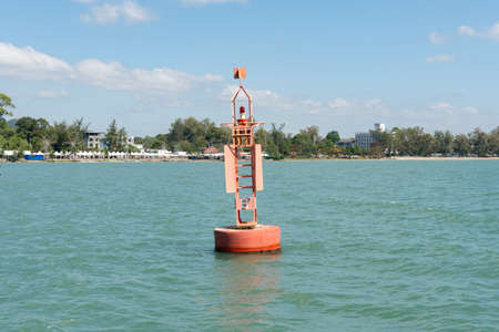 Red steel navigational floating buoy on blue sea,gulf of Thailand.