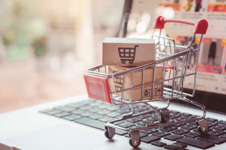 Shopping online. cardboard box with a shopping cart logo in a trolley on laptop keyboard. Shopping service on The online web. offers home delivery Imagens