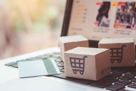 Shopping online. Credit card and cardboard box with a shopping cart logo on laptop keyboard. Shopping service on The online web. offers home delivery Stockfoto