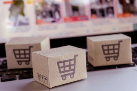 Online shopping. Cardboard box with a shopping cart   on laptop keyboard. Shopping service on The online web. offers home delivery Фото со стока