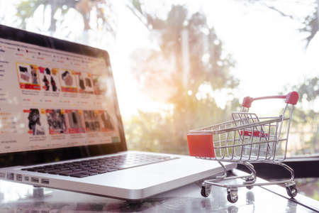 Online shopping concept - shopping cart or trolley and laptop on table