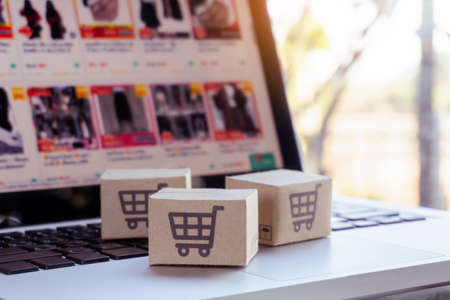 Online shopping. Cardboard box with a shopping cart logo on laptop keyboard. Shopping service on The online web. offers home delivery Фото со стока