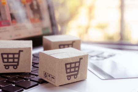 Online shopping. Credit card and cardboard box with a shopping cart   on laptop keyboard. Shopping service on The online web. offers home delivery