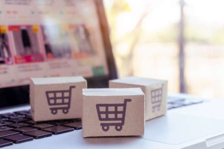 Online shopping. Cardboard box with a shopping cart  on laptop keyboard. Shopping service on The online web. offers home delivery