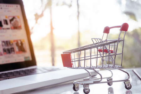Online shopping concept - shopping cart or trolley and laptop on table Archivio Fotografico