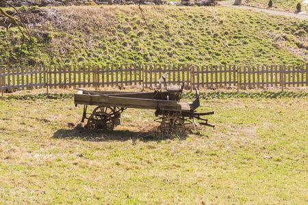 an old horse drawn carriage in a lonely field