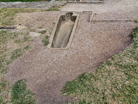 An open grave at an graveyard outside the city