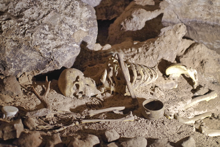 a skeleton in a cave at the ground