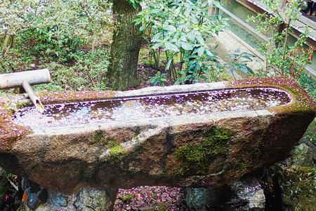 a stone fountain in a park in tokyo Banco de Imagens