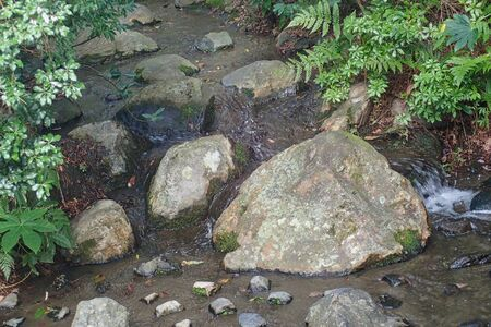 a small river with stones in the middle Stockfoto - 131594497