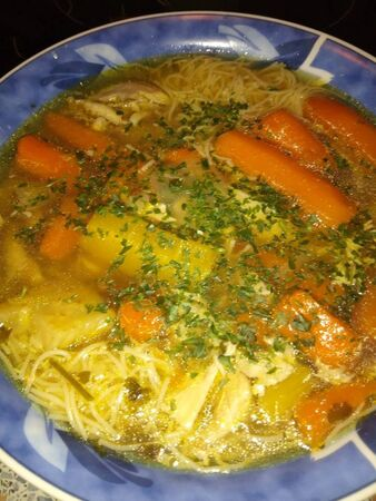 a soup with noodles and carrotts for meal