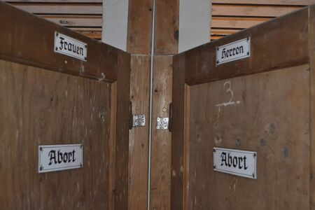 an old toilet door for men and woman in german language sign