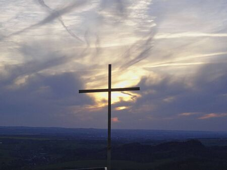 a cross on the mountains top at sunset in summer