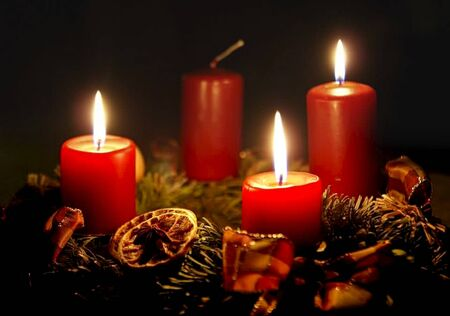 an Advent wreath with burning candles on it