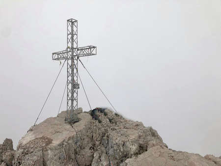 a cross on the mountains top with blue sky