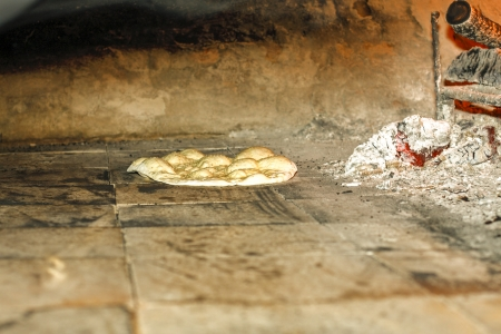 Flat bread baking in a traditional Turkish brick oven photo