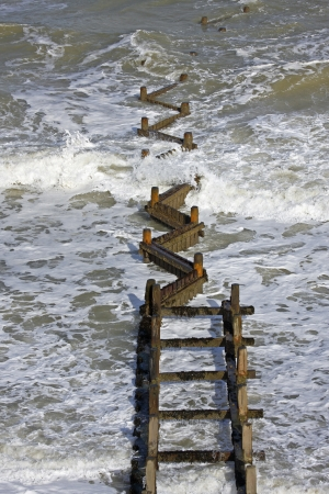 groynes: Waves breaking over a wooden breakwater, groynes which form part of Britain�s coastal defences  Stock Photo