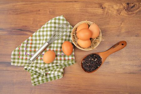 Top view of raw eggs in the basket and Straw or chaff with Egg beater , hand towel and rice berry in the wooden spoon on wooden table.