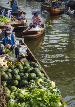 laden: THAILAND DAMNOEN SADUAK - march 03,2016 : Damnoen Saduak Floating Market Featuring many small boats laden with colourful fruits, vegetables and Thai cuisine Editorial