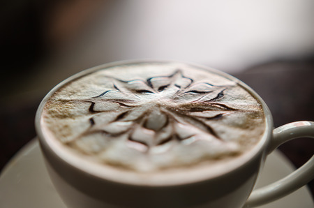 steel. milk: Barista making a cup of coffee soft focus image .