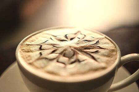 steel. milk: Coffee cappuccino on a wooden table Soft-focus image and filter lens flare