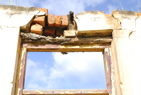 Blue sky shines in through the fanlight above the doorway of a dilapidated house  Stock Photo