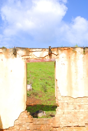 doorframe: A doorway in a ruin of a house leads to a green field