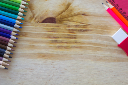 School and drawing supplies, on wooden table. Colored pencils, eraser, pencil and ruler. With copy space.