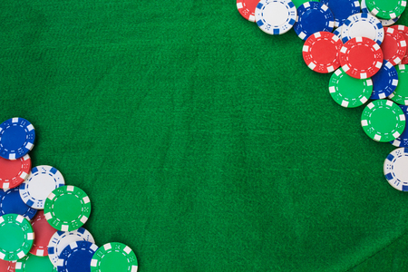 Colorful gambling chips on green felt background with copy space.