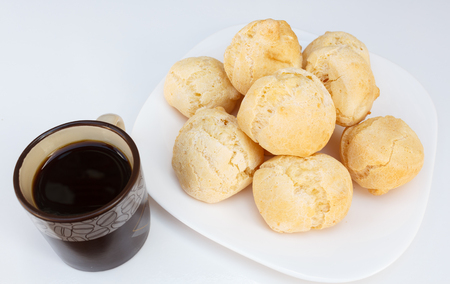 Brazilian breakfast, cheese bread (pao de queijo) served on dish on white table with coffee.