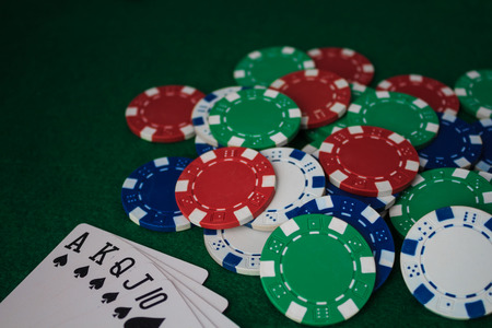Hand of Poker, straight flush and chips on a felt green background. Top view and copy space. Stock Photo